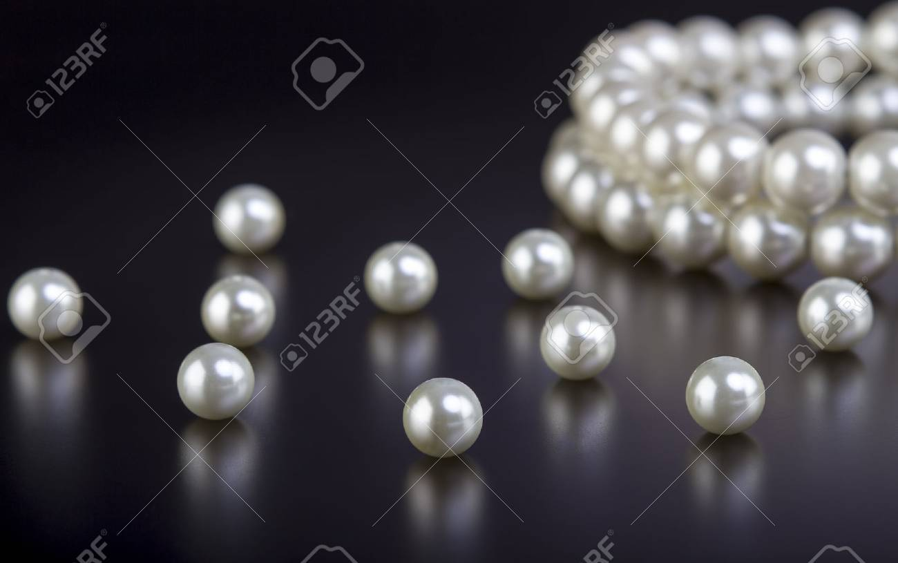 White pearls necklace on black background - 39636222