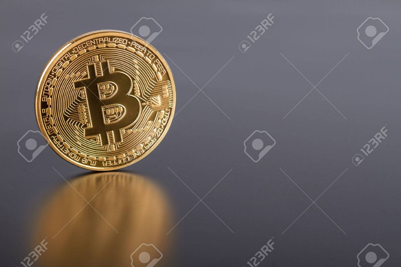 Studio shot of golden Bitcoin virtual currency on gray. Close-up of front side. - 40940724