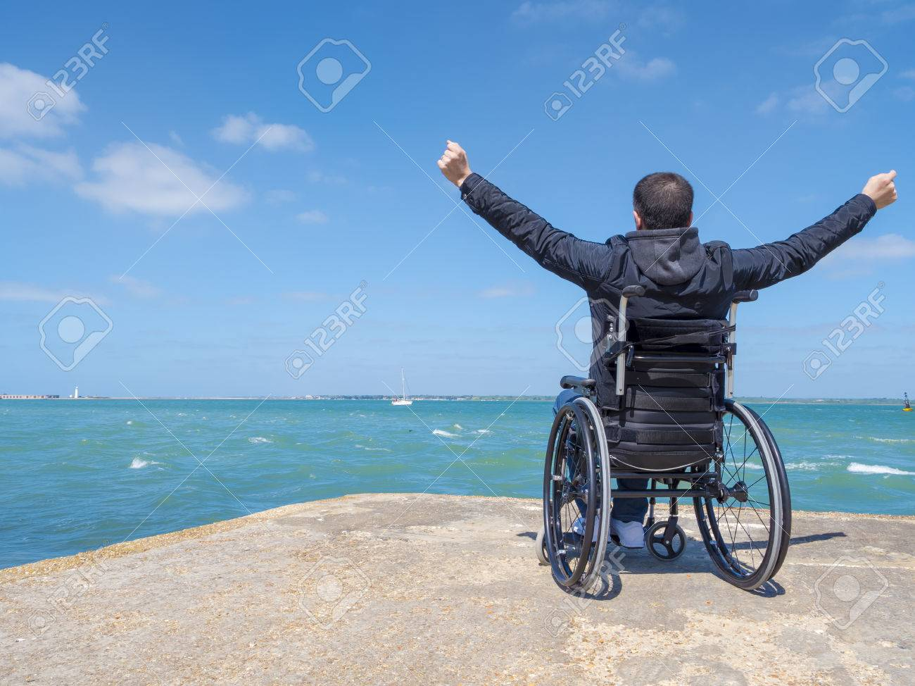 Disabled alone young man sitting in a wheelchair and looks at the sea. - 79446821