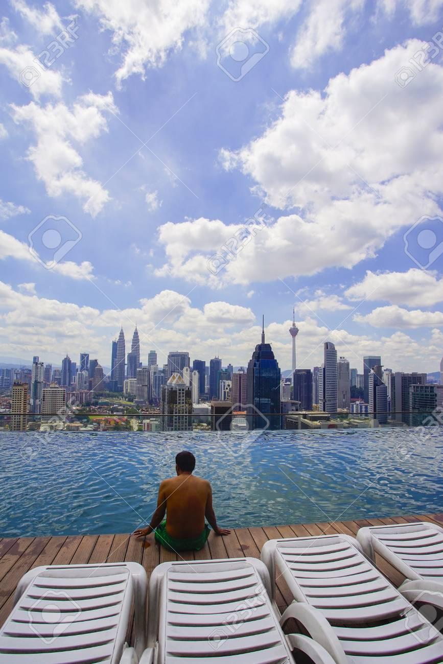 A Traveller Sitting On Rooftop Swimming Pool Watching Kuala Lumpur Skyline  View Stock Photo   89177655