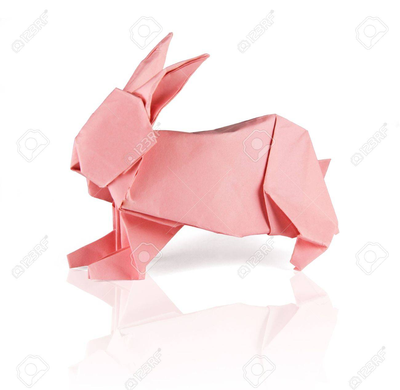 Pink Origami Rabbit On The White Reflecting Background Stock Photo