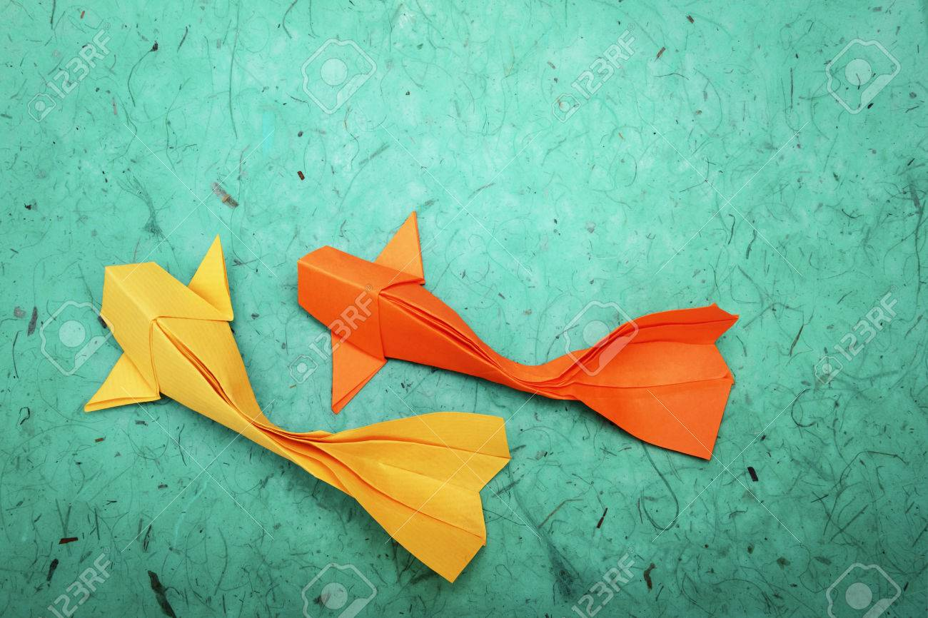 Origami Paper Goldfish Group On A Green Water Background Stock Photo