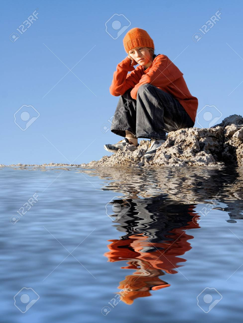 bored lonely child sitting by sea Stock Photo - 2634711
