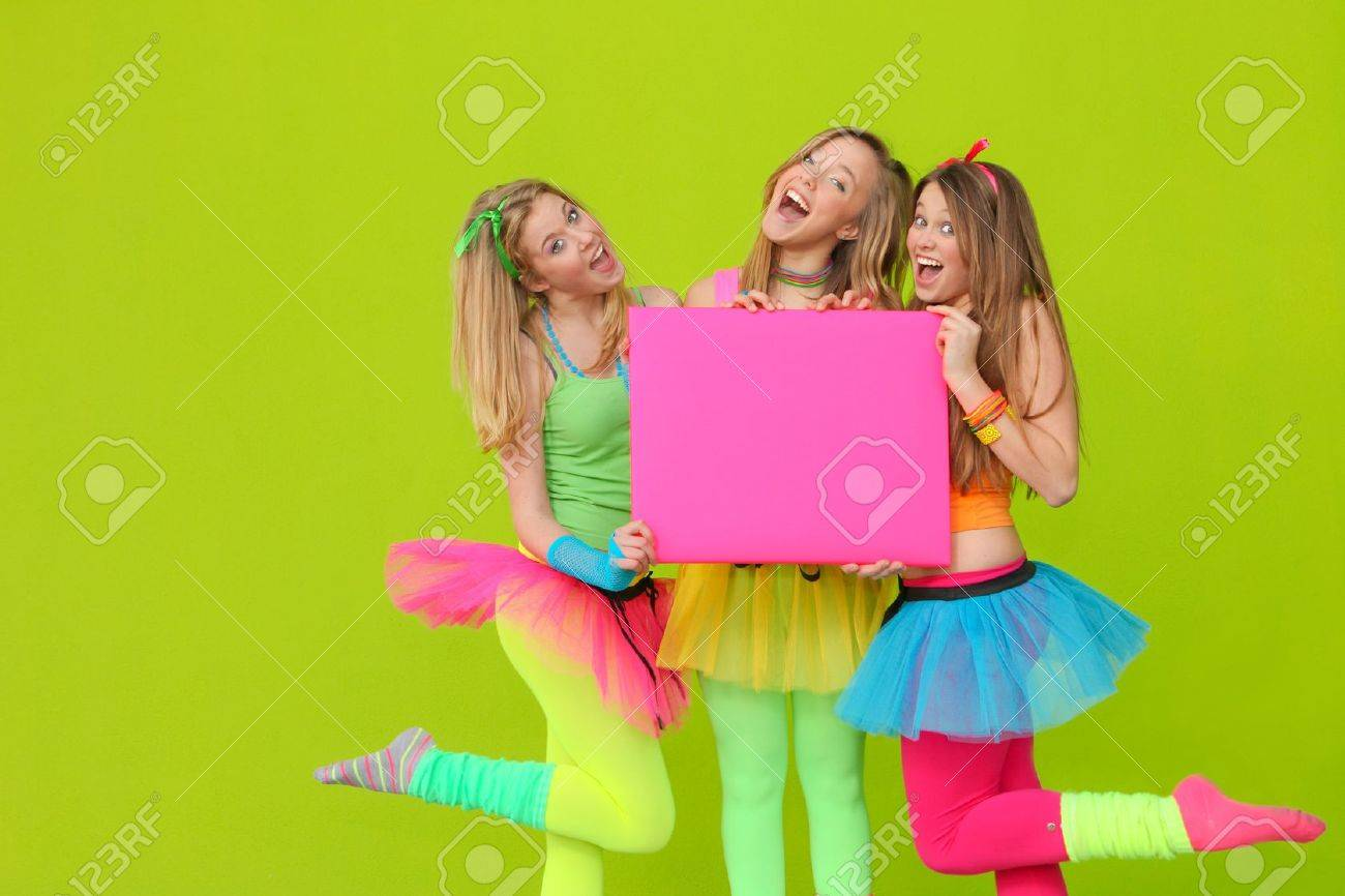 happy party teen girls in neon fancy dress clothing with blank board Stock Photo - 10135188