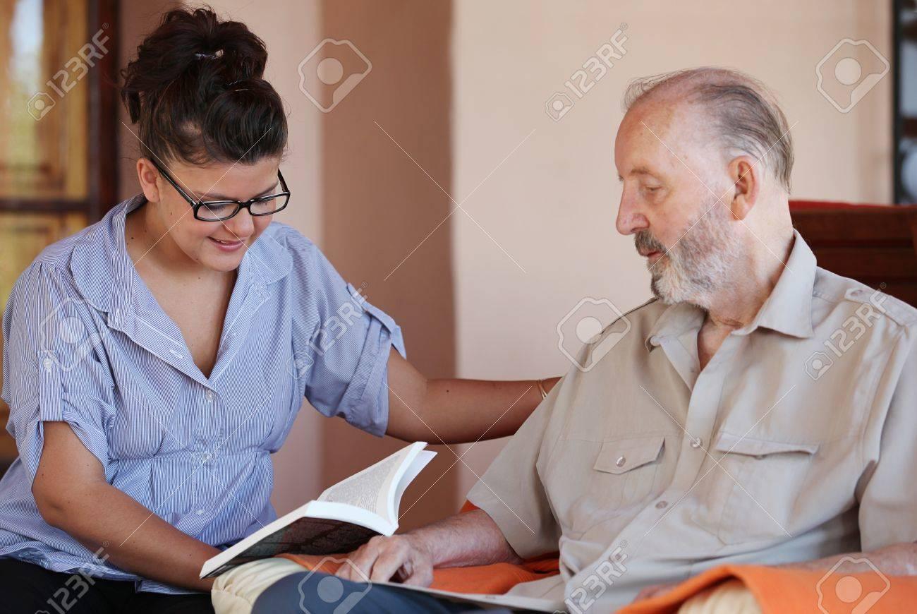 carer reading to senior Stock Photo - 11409799
