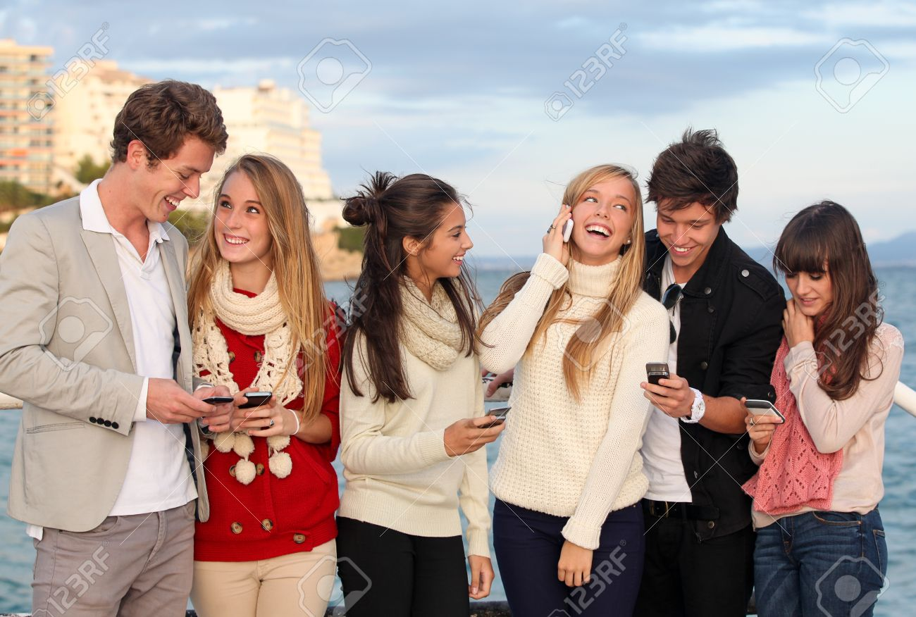 group of happy smiling teens, kids, texting and calling with mobile or cell phones Stock Photo - 14996101