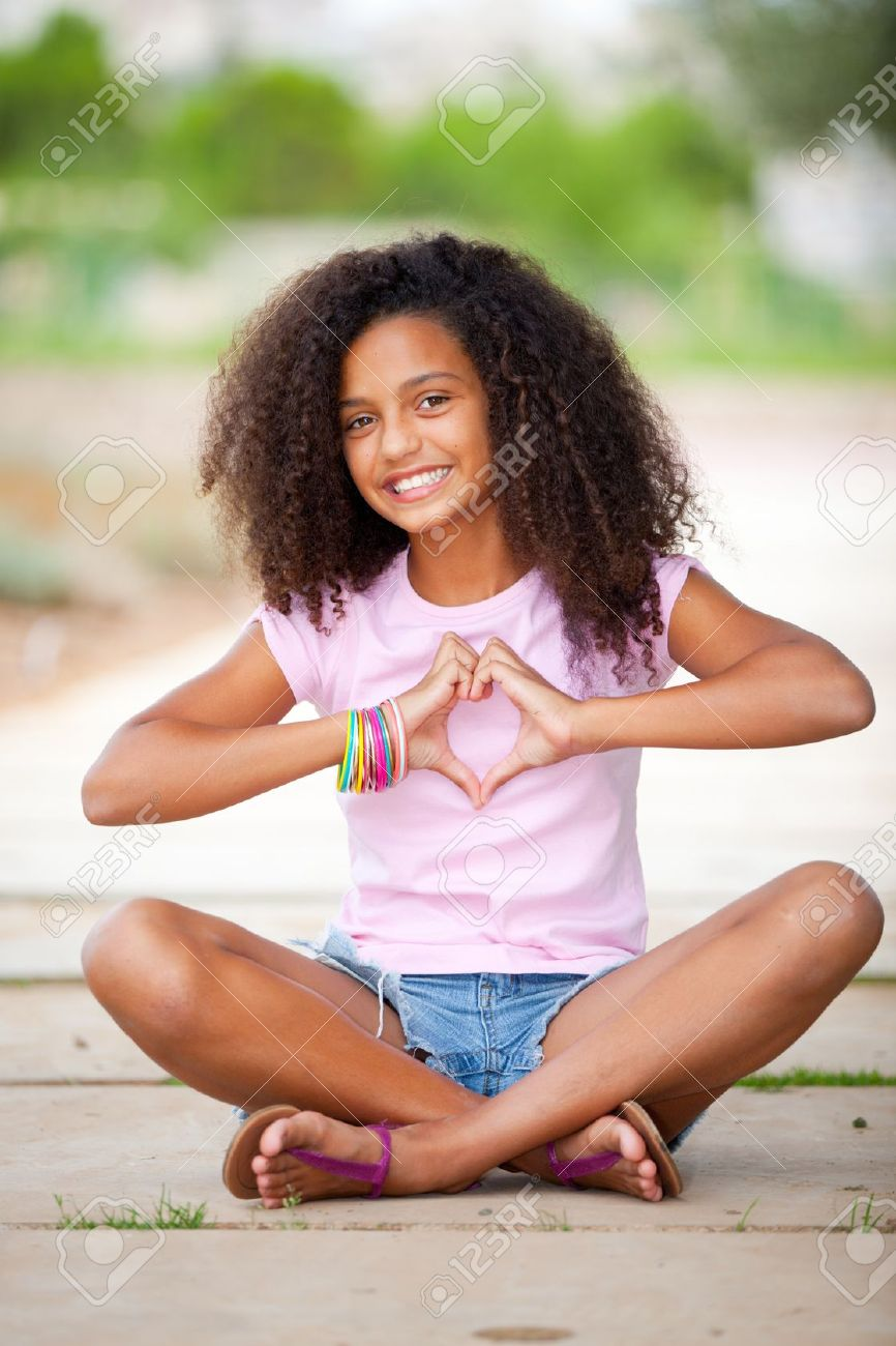 young blakc young happy smiling african american black teen girl with afro hair making  heart shape