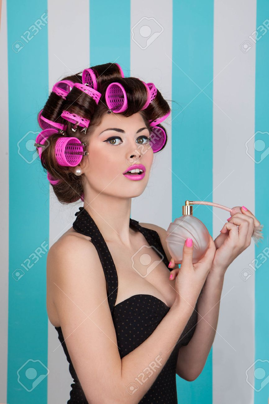 Retro Pin Up Girl Spraying Perfume With Hair Rollers And Makeup