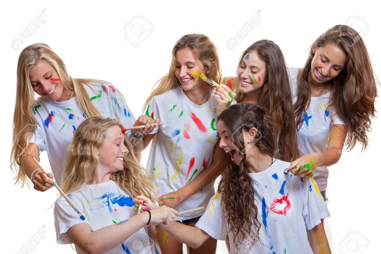 group of kids or teens girls having fun with messy paint stock photo