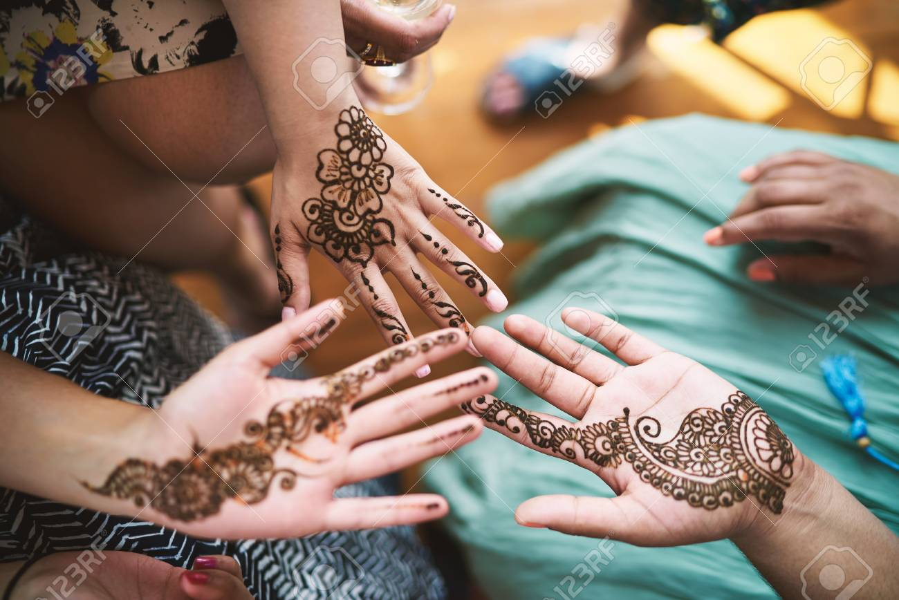 Indian women showing hand with henna tattoo art (Mehndi) on the..