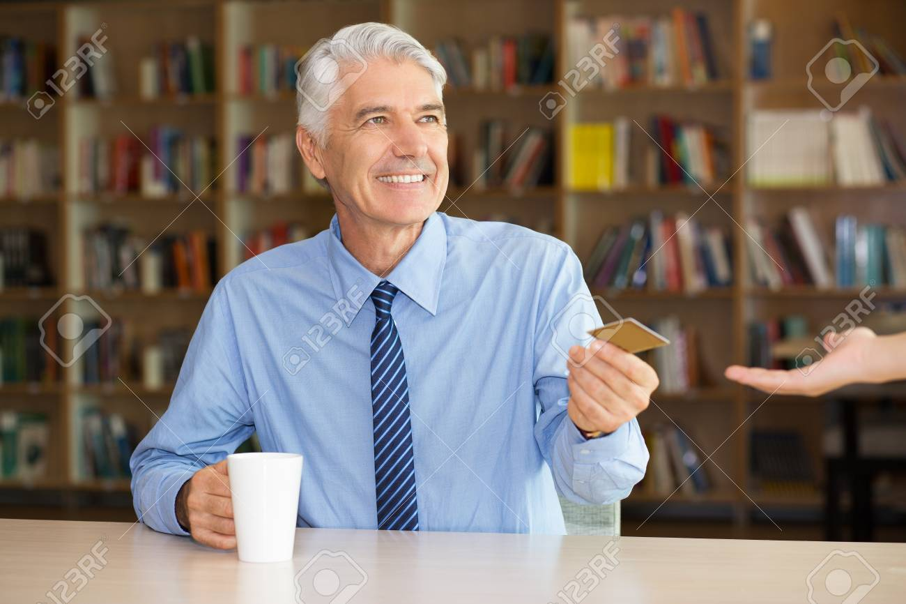 Happy senior businessman giving credit card to waitress to pay for coffee. Positive manager drinking coffee at table in library. Banking or convenient service concept - 67105014