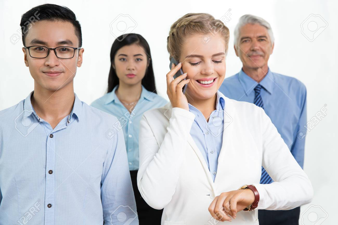 Detalle De Los Cuatro Hombres De Negocios Jóvenes Y Mayores De Pie Y  Sonriendo A La Cámara. Mujer En Primer Plano Está Hablando Por Teléfono  Móvil Y Mirando ... 4da7a8c95519