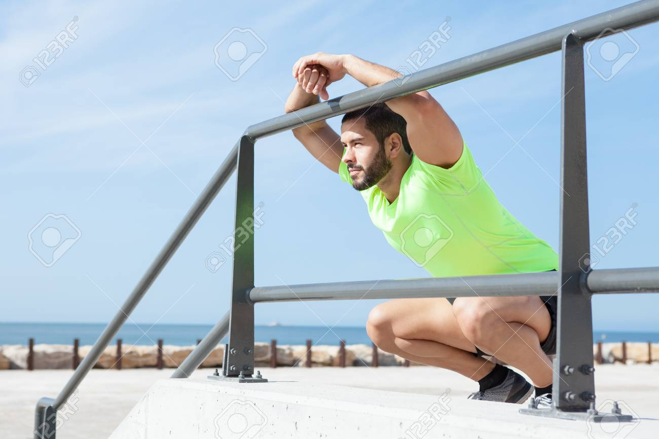 relaxed sporty man sitting and leaning on railing stock photo