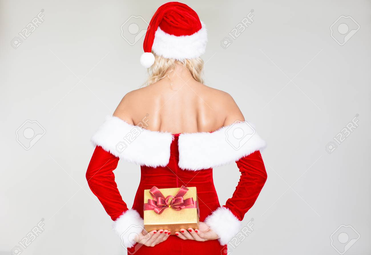 bb8a5d82d77 Rear view of woman in Santa hat holding gift box Stock Photo - 90259272