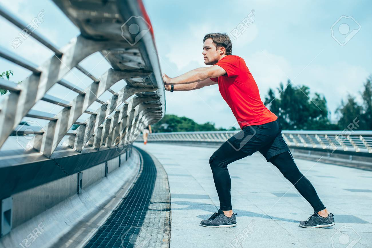 serious man stretching calf and leaning on railing stock photo