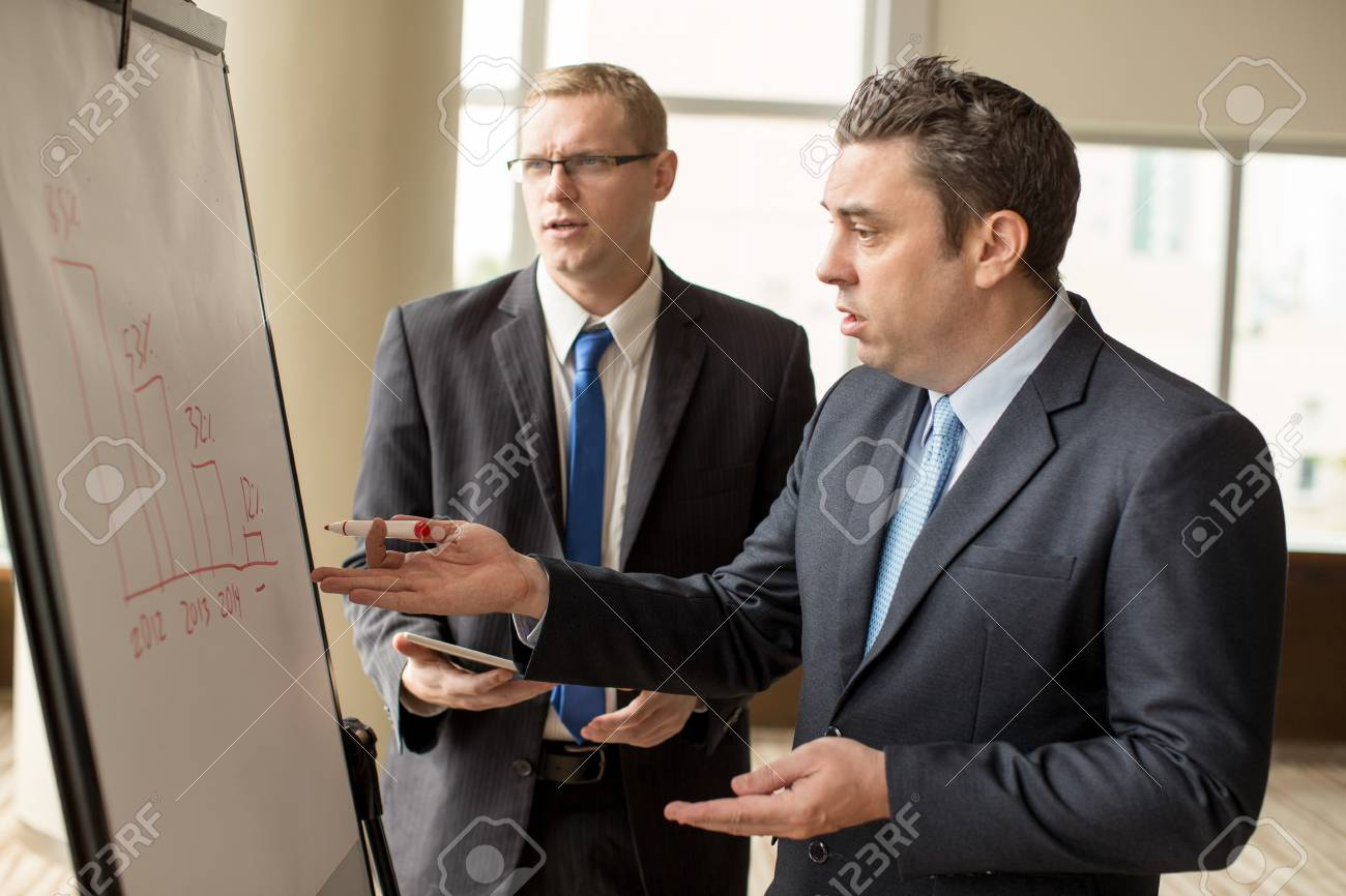 Two upset business men looking at decrease diagram stock photo stock photo two upset business men looking at decrease diagram ccuart Images