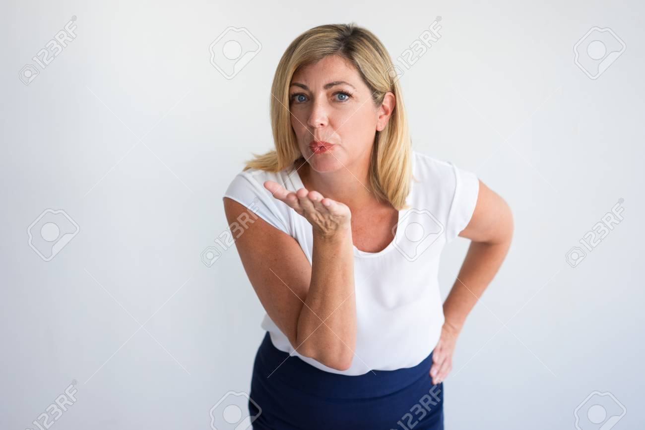 950f1400dc9c Serious mature Caucasian woman posing and blowing kiss at camera. Woman  illustrating femininity and attraction