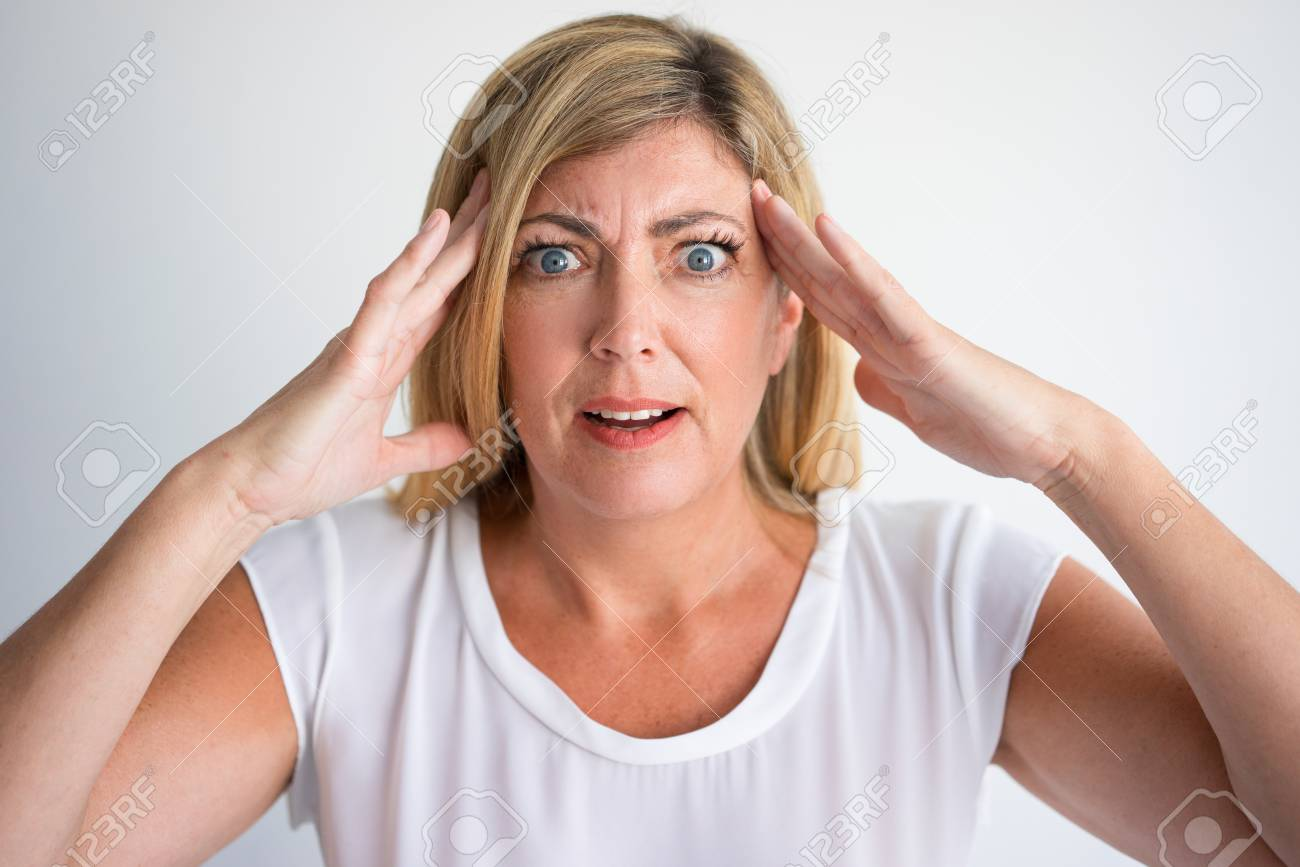 50ee8da92414 Shocked mature Caucasian woman with wide eyes and questioning face touching  temples. Closeup of angry