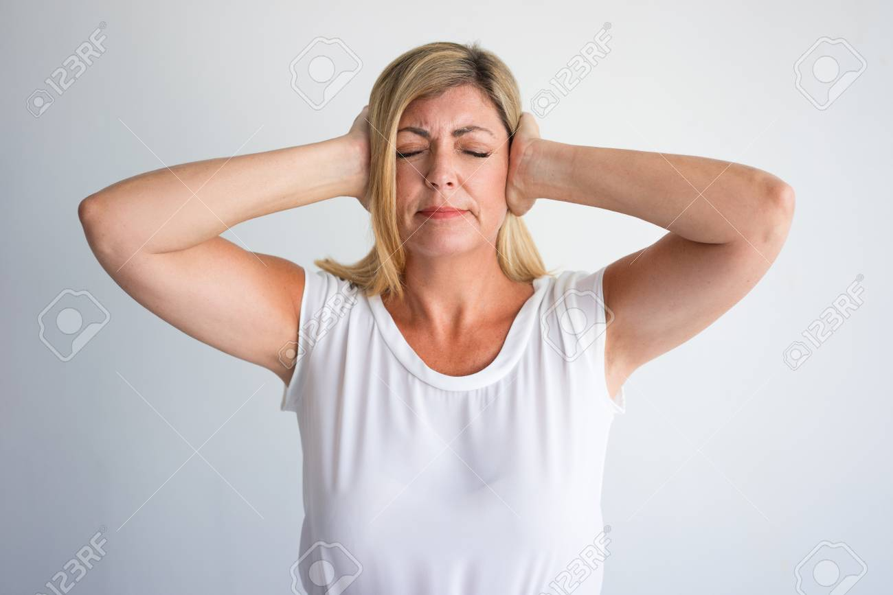 83280682e185 Stock Photo - Upset mature Caucasian woman with closed eyes covering ears  with hands. Strict middle aged lady suffering from great noise or loud  music.