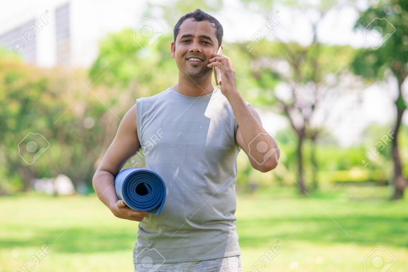 citizen office concept. Happy Citizen Changing Office Work For Yoga Class. Young Content Indian Man Walking In Park Concept