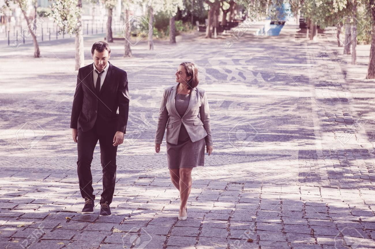 Optimistic business colleagues walking over street and chatting. Smiling businesswoman in gray dress talking to male manager during stroll in summer.