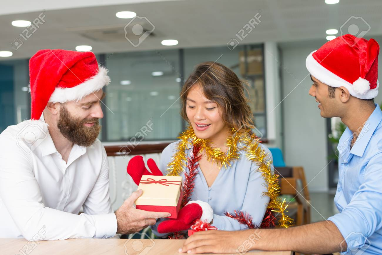 Gifts For Employees For Christmas.Cheerful Boss Giving Christmas Gifts To Employees Bearded Young