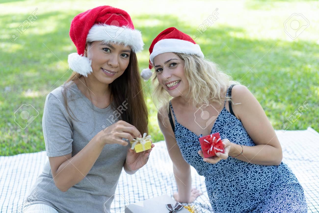 Ladies Christmas Gifts.Smiling Ladies Unpacking Christmas Gifts In Park Beautiful Women