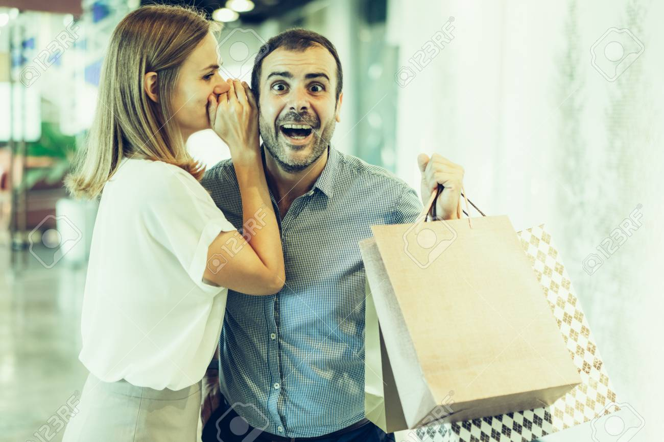 9da392d672cc Stock Photo - Young woman sharing good news with husband during shopping.  Blonde woman in casual wear whispering in mans ear