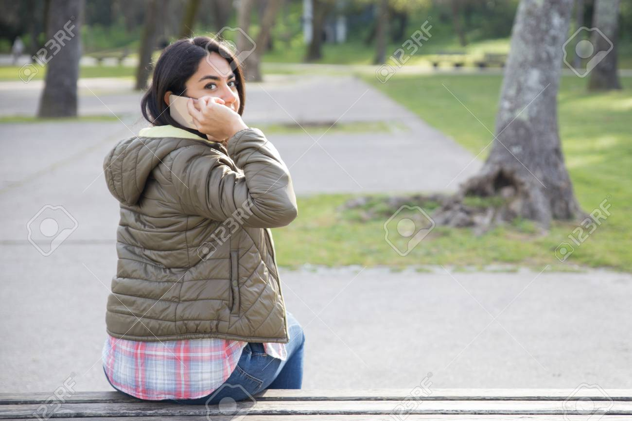 Rear view of student girl talking on phone in park. Young woman in casual jacket sitting on bench, speaking on cell and turning head round. Phone talk concept - 121991165