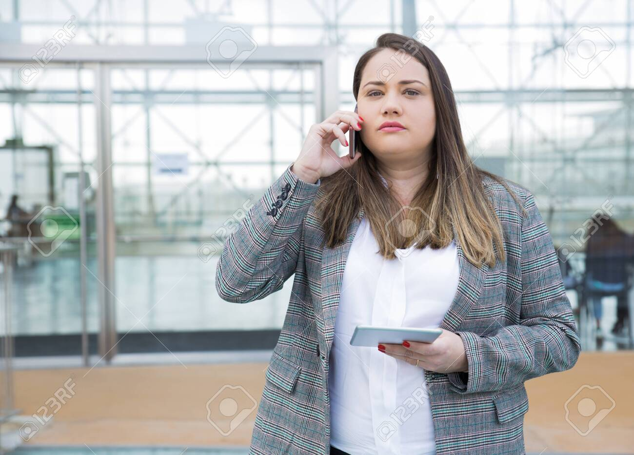 Serious female executive posing in office lobby while speaking on phone. Young woman in formal jacket holding tablet, talking on cell and looking at camera. Business and gadgets concept - 123136052