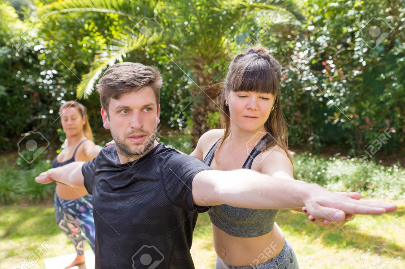 Focused yoga instructor helping newby to cope with warrior pose. Man doing yoga outdoors, woman adjusting his hands. Training yoga concept - 123848391