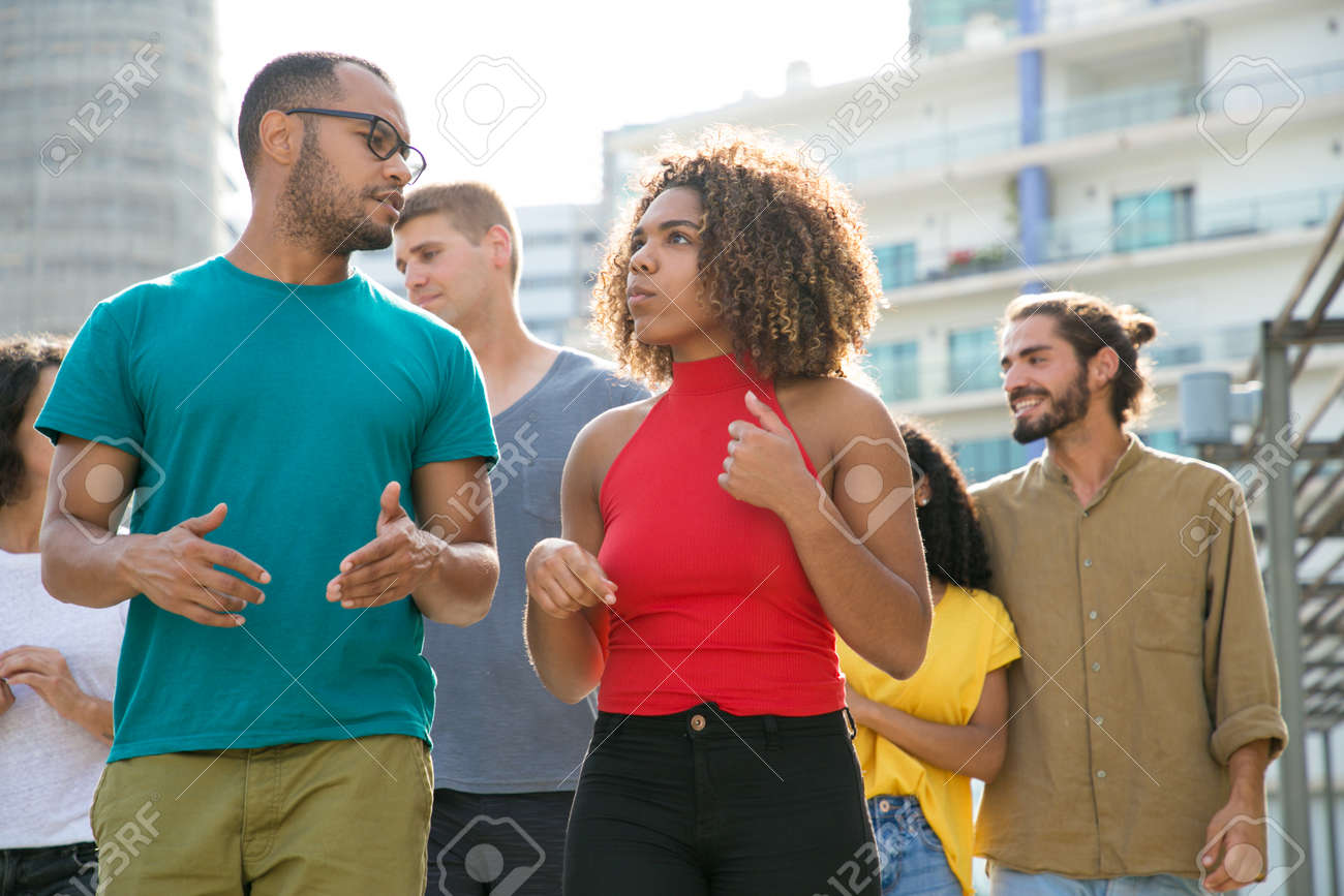 Interracial team of friends walking outside. Young men and women in casual enjoying walk, talking, discussing news. Communication and lifestyle concept - 131918353