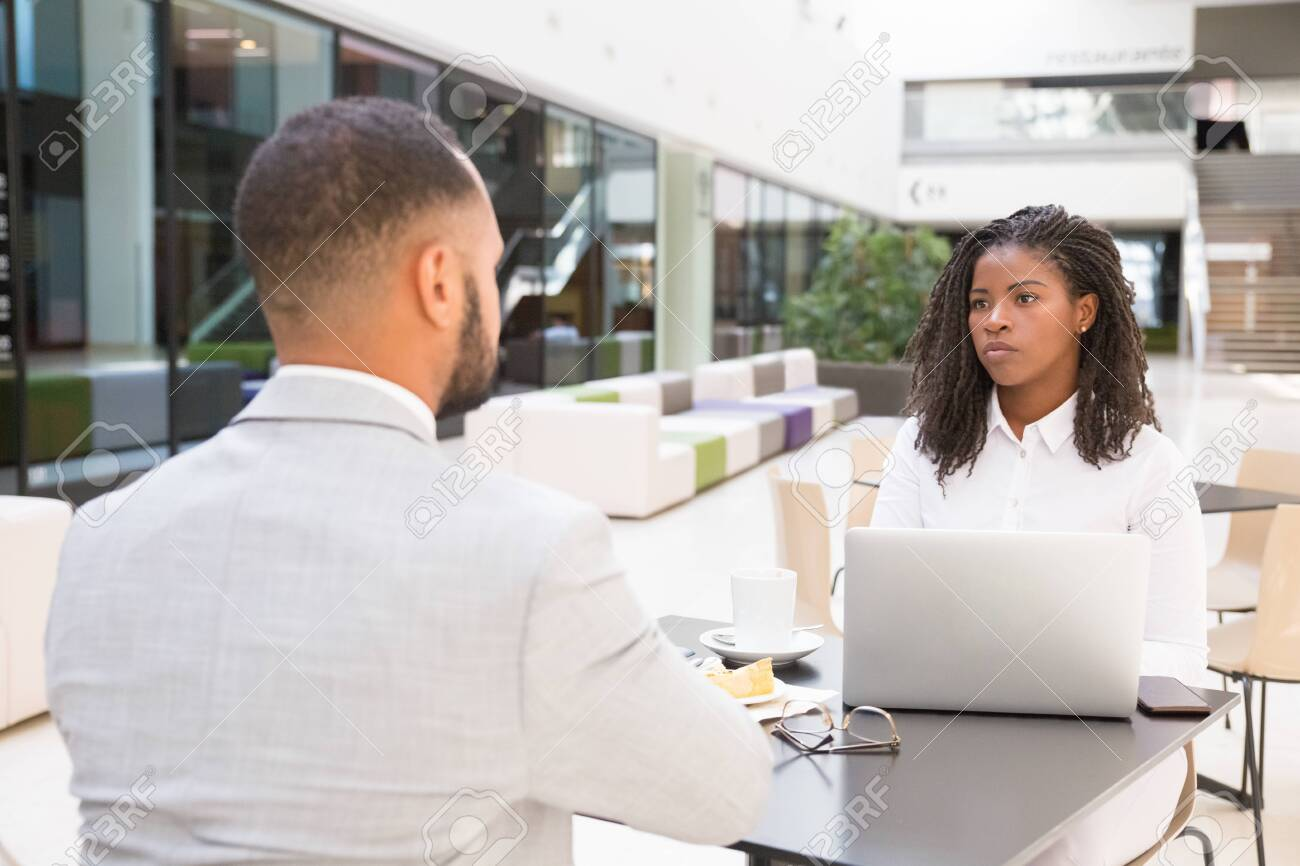 Young businesspeople having lunch break together. Business man and woman sitting at table in cafe, using laptop and talking. Lunch break or meeting concept - 129804894
