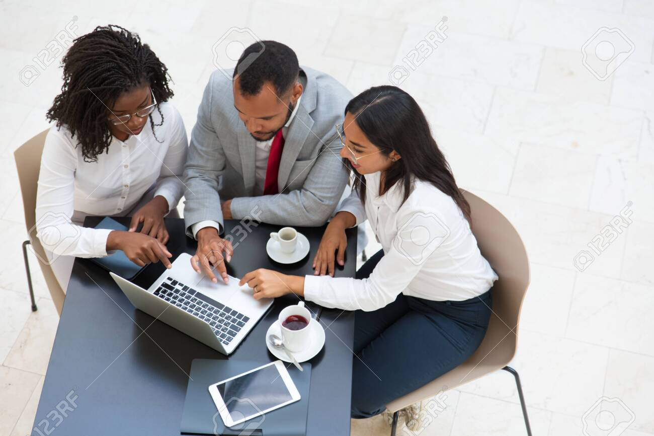 Diverse business group working on laptop during coffee break. Business man and women sitting at table with tablet and cups, using computer and talking. Digital tools concept. - 129805180