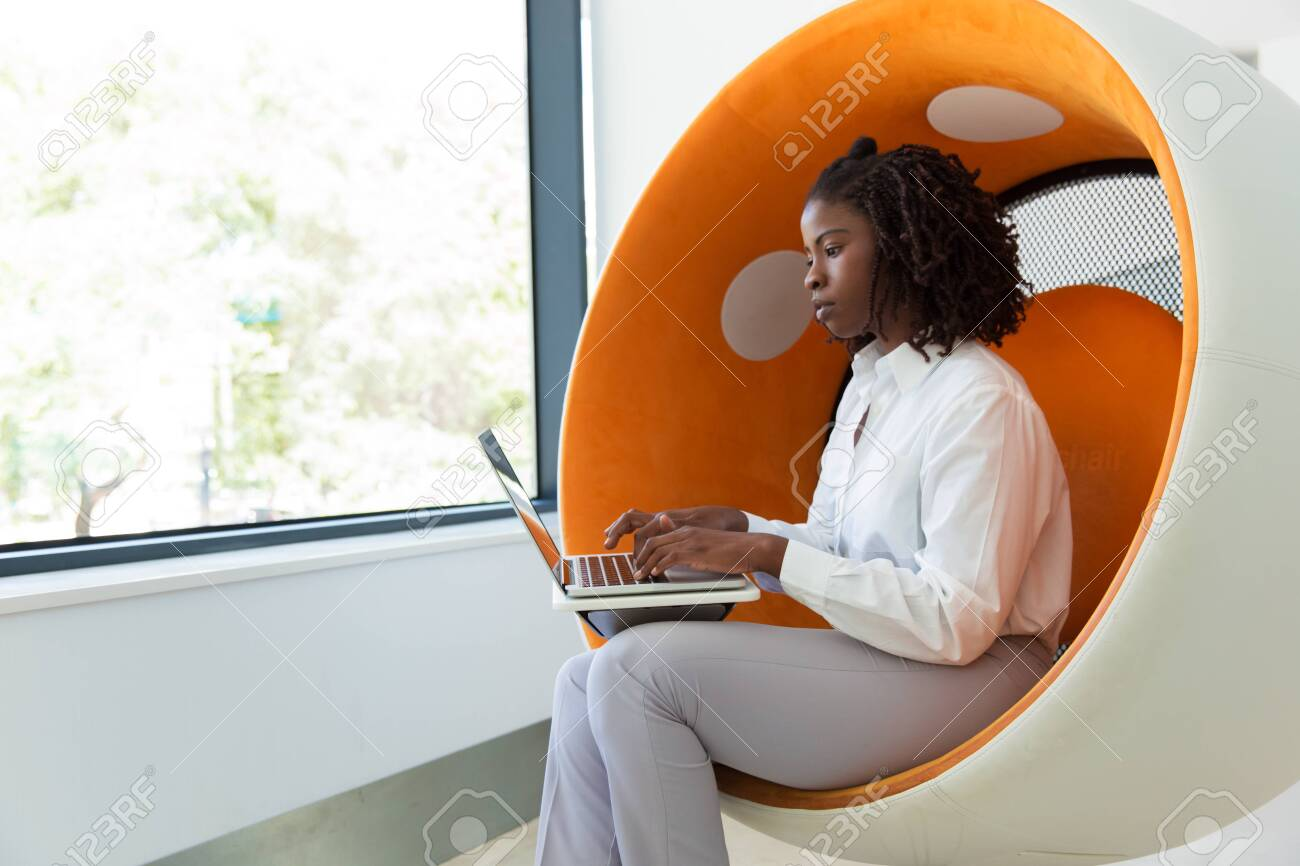 Serious young female professional working on computer in office rest room. Black business woman sitting in interactive chair, using laptop, typing and looking at screen. Busy professional concept - 130048374