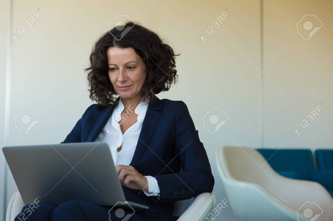 Satisfied businesswoman working on computer in office lounge and getting good news. Business woman sitting in armchair, using laptop, looking at screen and smiling. Wi-Fi concept - 130048861