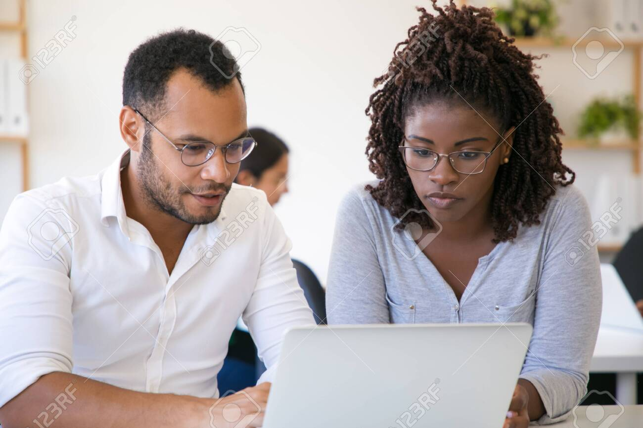 Diverse colleagues watching content on laptop together. Young man and woman using computer in office, looking at screen and talking. Corporate discussion concept - 130777911