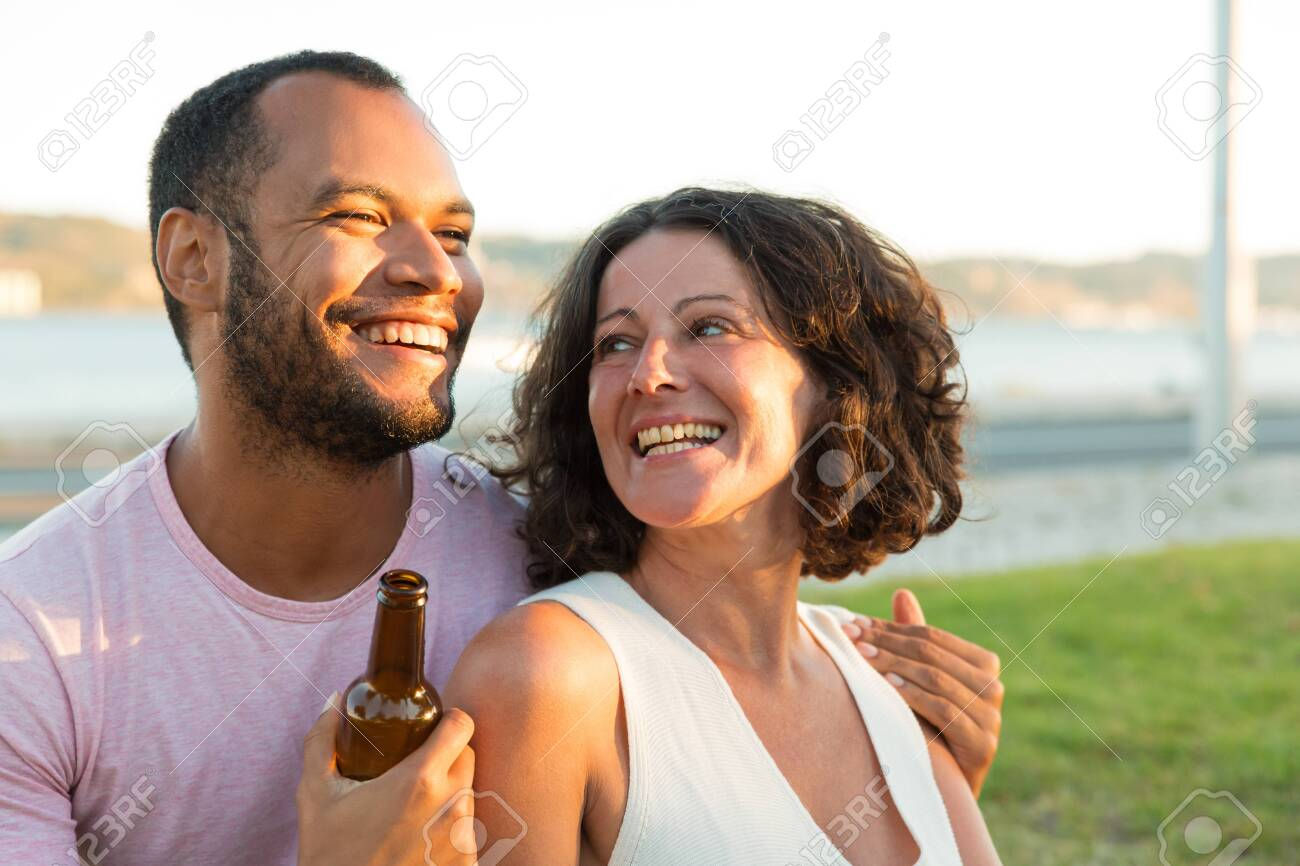Happy relaxed couple drinking beer, and chatting outdoors. Man and woman sitting on grass, hugging, holding beer bottle and laughing. Dating outdoors concept - 134767146
