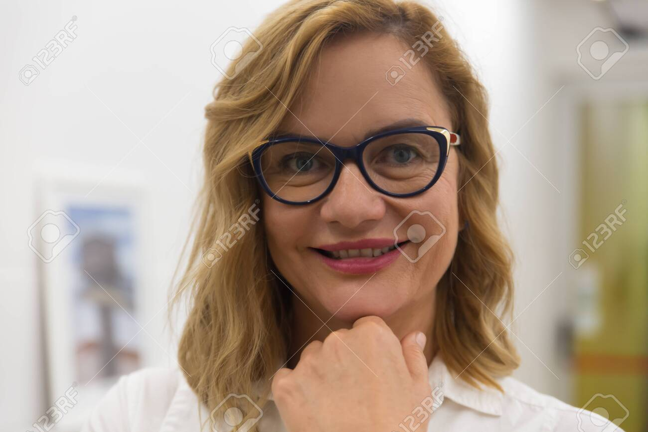 Confident businesswoman smiling at camera. Close-up portrait of beautiful middle aged businesswoman in eyeglasses standing with hand on chin and smiling at camera. Business concept - 134497618