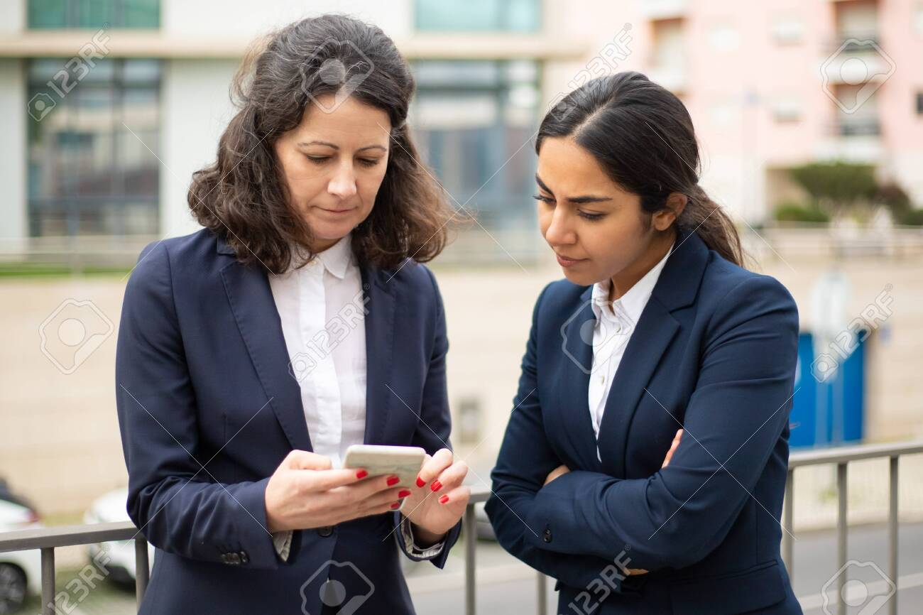 Serious businesswomen using smartphone. Female colleagues in formal wear standing on street and using cell phone together. Business and technology concept - 142038949