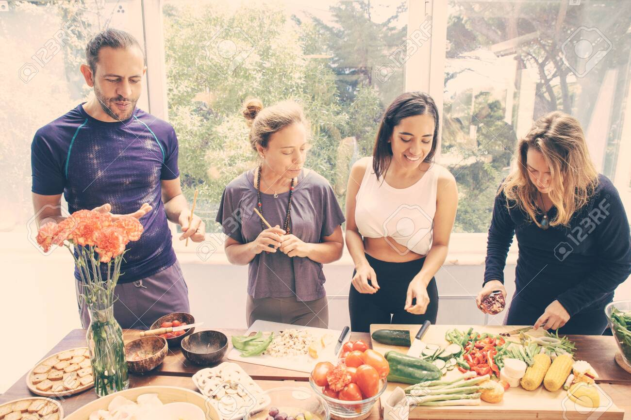 Cheerful friends preparing healthy meal. Happy young man and women in sportswear standing at table with raw organic fruits and vegetables. Healthy eating concept - 143740491
