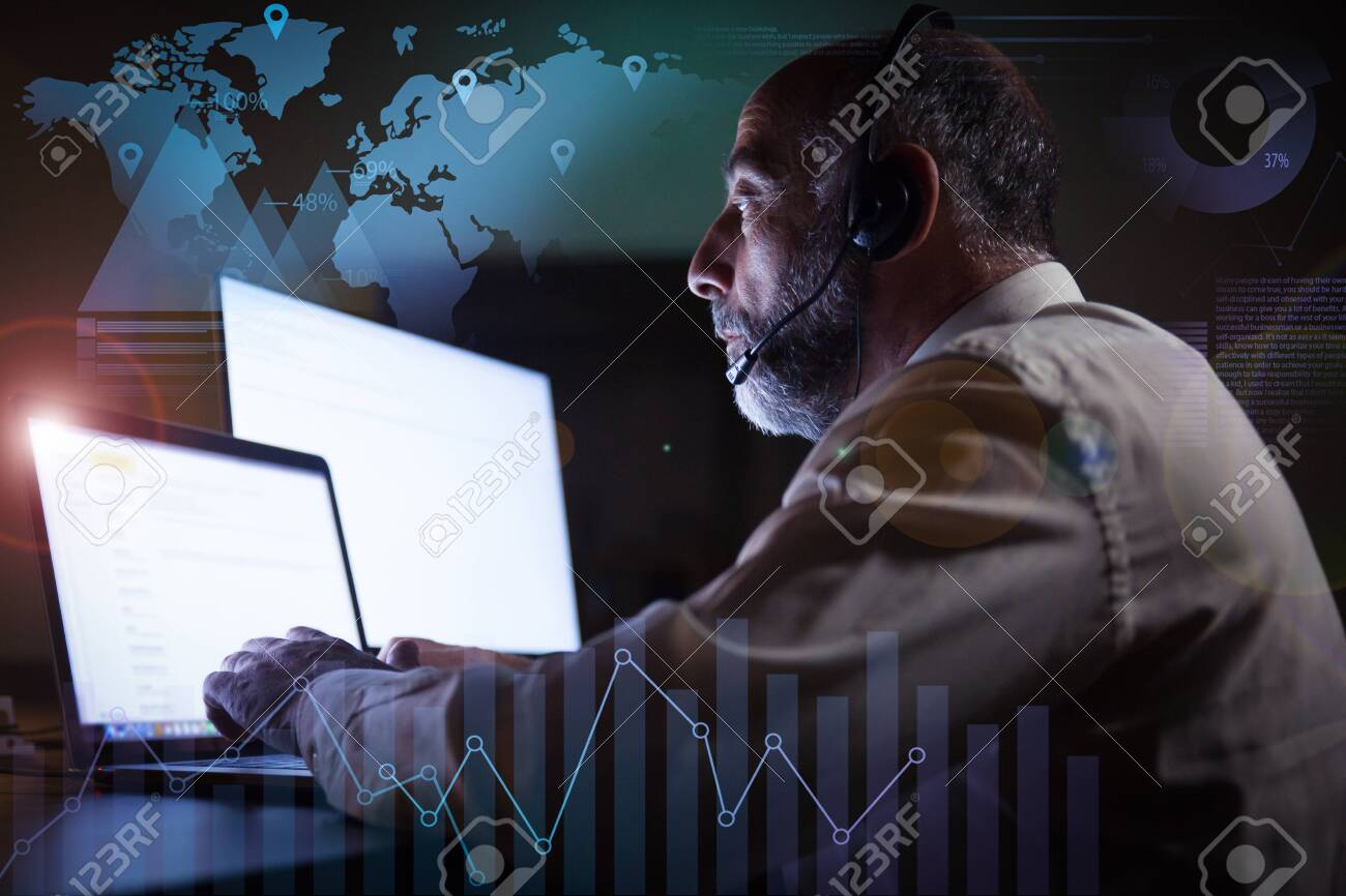 Man in headset using laptop and virtual statistic graphics. Side view of focused mature male call center operator in headset working with computer in dark office. Customer support concept - 144369055