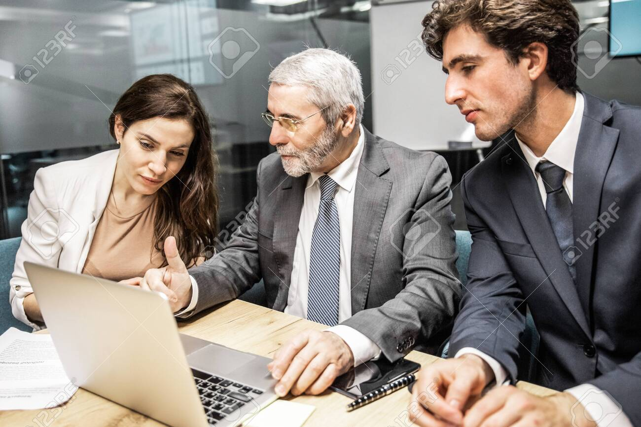 Confident business team looking at laptop. Group of office employees sitting at table and discussing new project. Business, teamwork concept - 145407937