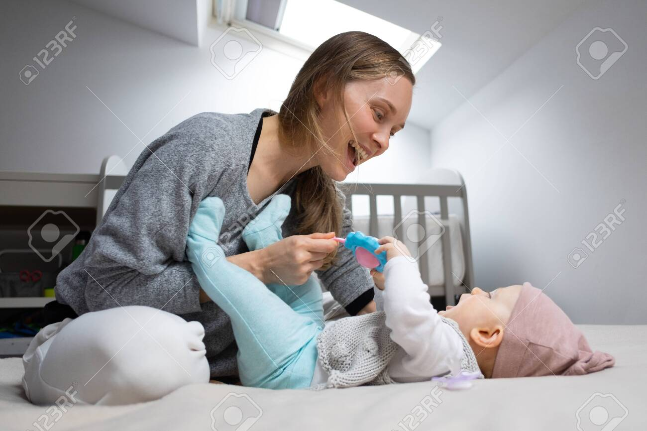 Joyful mom entertaining baby with rattle toy, having fun with daughter in bedroom. Mother and little child staying at home. Child care or isolation concept - 147328287