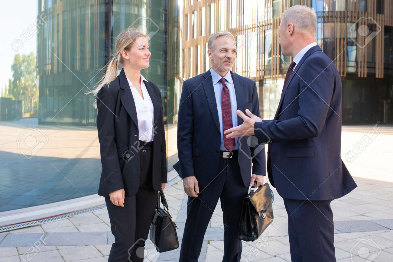 Confident professional adult businesspeople meeting outdoors. Content business man and woman in suit listening boss and smiling. Teamwork, negotiation and partnership concept - 151535356