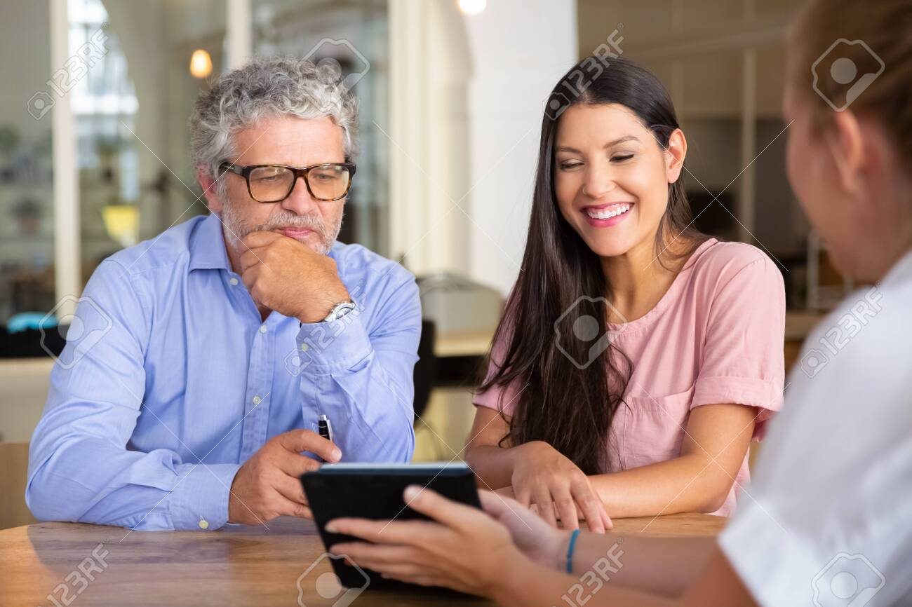 Happy young woman and mature man meeting with professional, watching and discussing content on tablet and laughing. Consulting or satisfied customers concept - 154521211