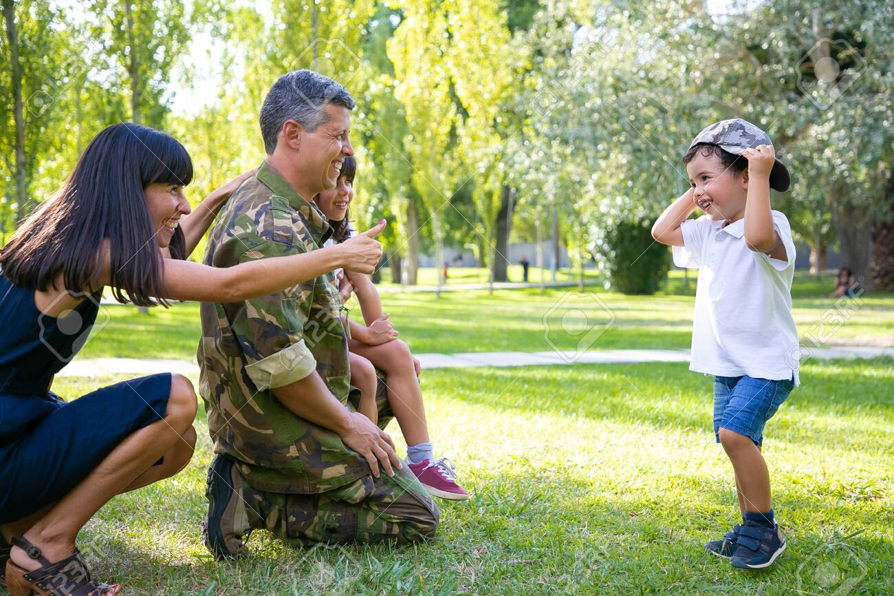 Happy military father in uniform returning to family. Children with mom meeting dad, boy trying on camouflage cap. Family reunion or returning home concept - 158058403