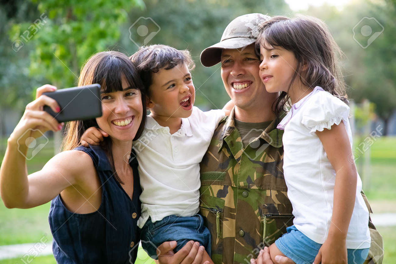 Happy joyful military family celebrating dads returning, enjoying leisure time in park, taking selfie on smartphone. Medium shot. Family reunion or returning home concept - 158390585