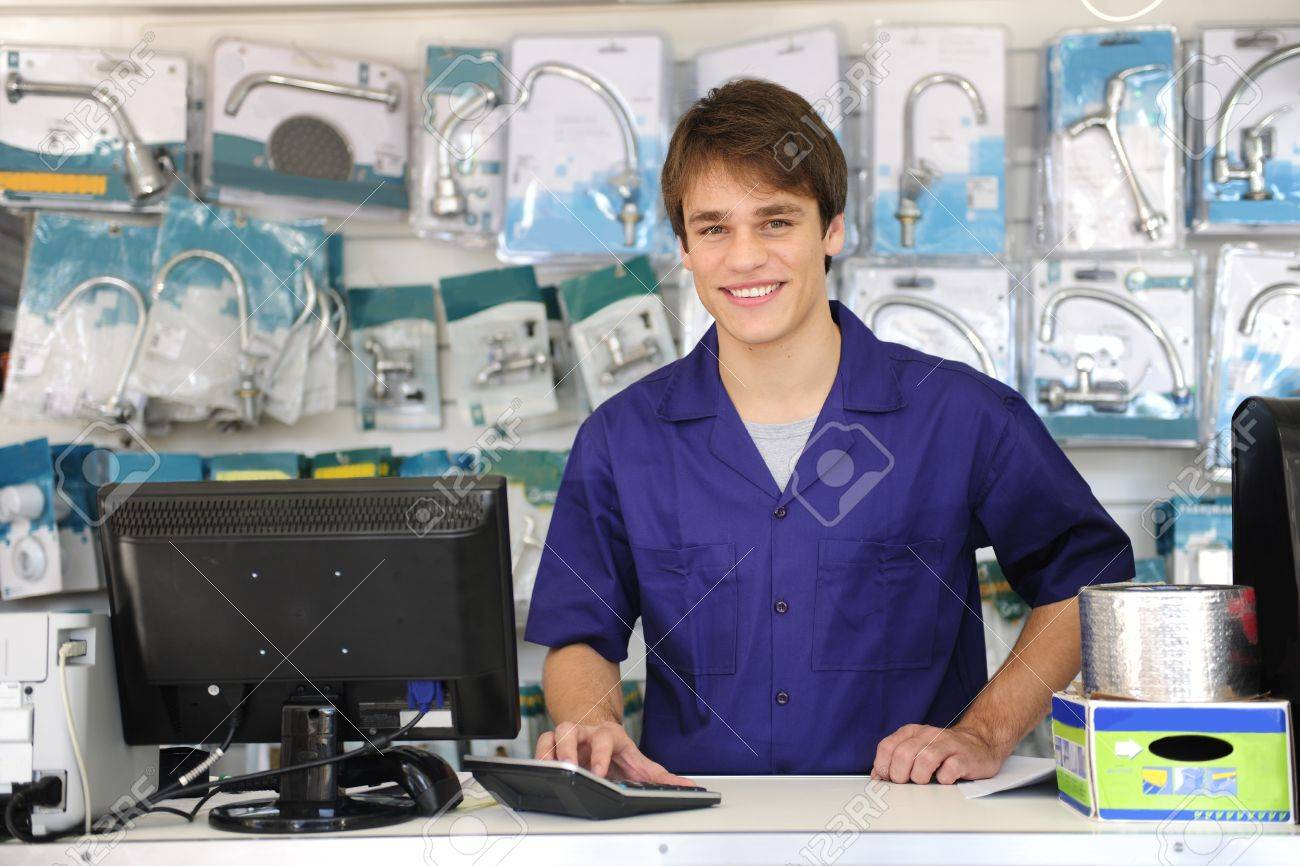 portrait of a sales assistant behind the counter of a building    stock photo   portrait of a  s assistant behind the counter of a building center