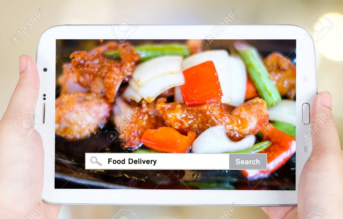 Hand holding tablet with food delivery words on search bar over hand holding tablet with food delivery words on search bar over food background food online forumfinder Image collections